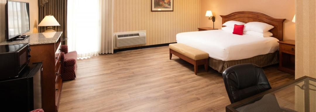 Wood floors in guest room with king bed