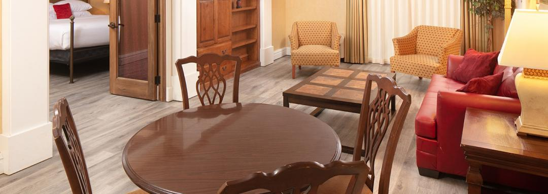 Guest room with lounge chairs, dining table with four chairs, leather couch, and coffee table