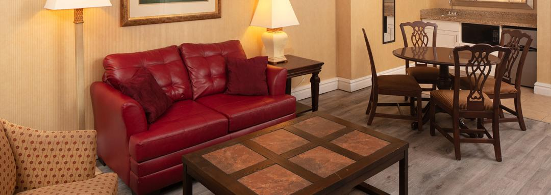 Guest room with kitchenette, dining table with four chairs, red leather couch, and coffee table
