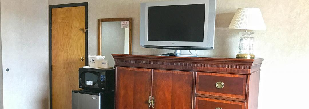Guest Room with Room Amenities Including TV, Microwave, and Mini Fridge
