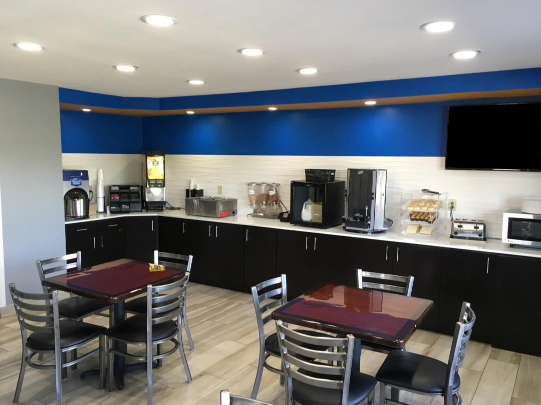 Breakfast bar with juice, coffee, and food options with tables and chairs