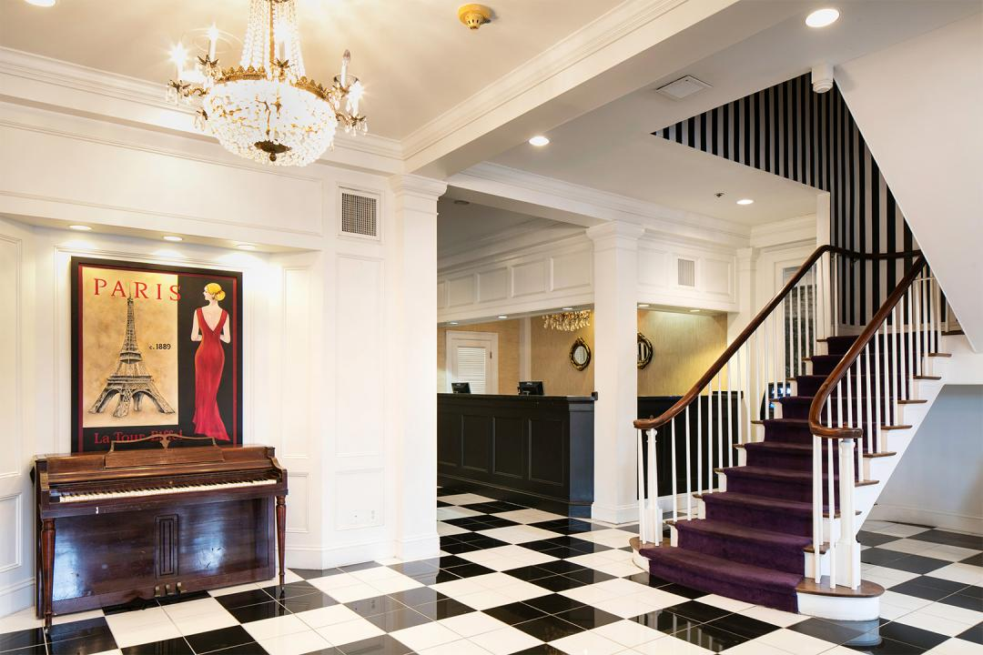 Hotel front desk and lobby area with checkered tile floor and stairs leading to second floor