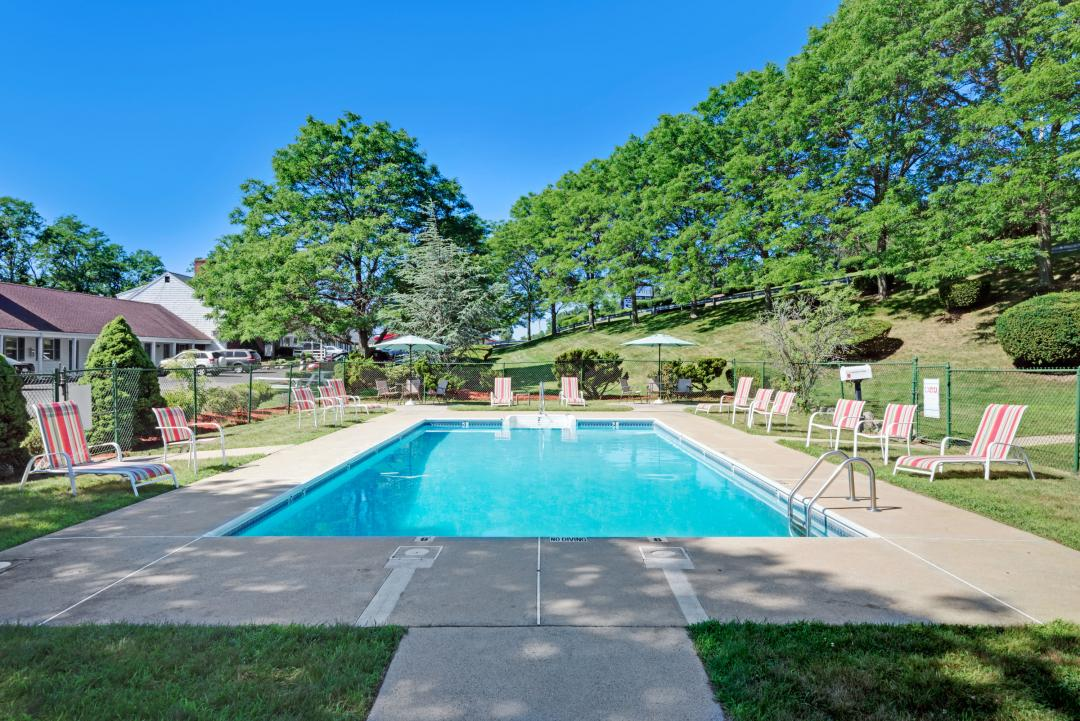 Outdoor Pool Area with ample Seating and Chaise Lounges