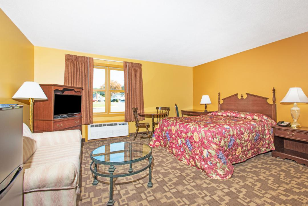 Guest room with queen bed, sofa, table, and two chairs
