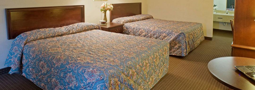 Hotel guestroom with two queen beds and table
