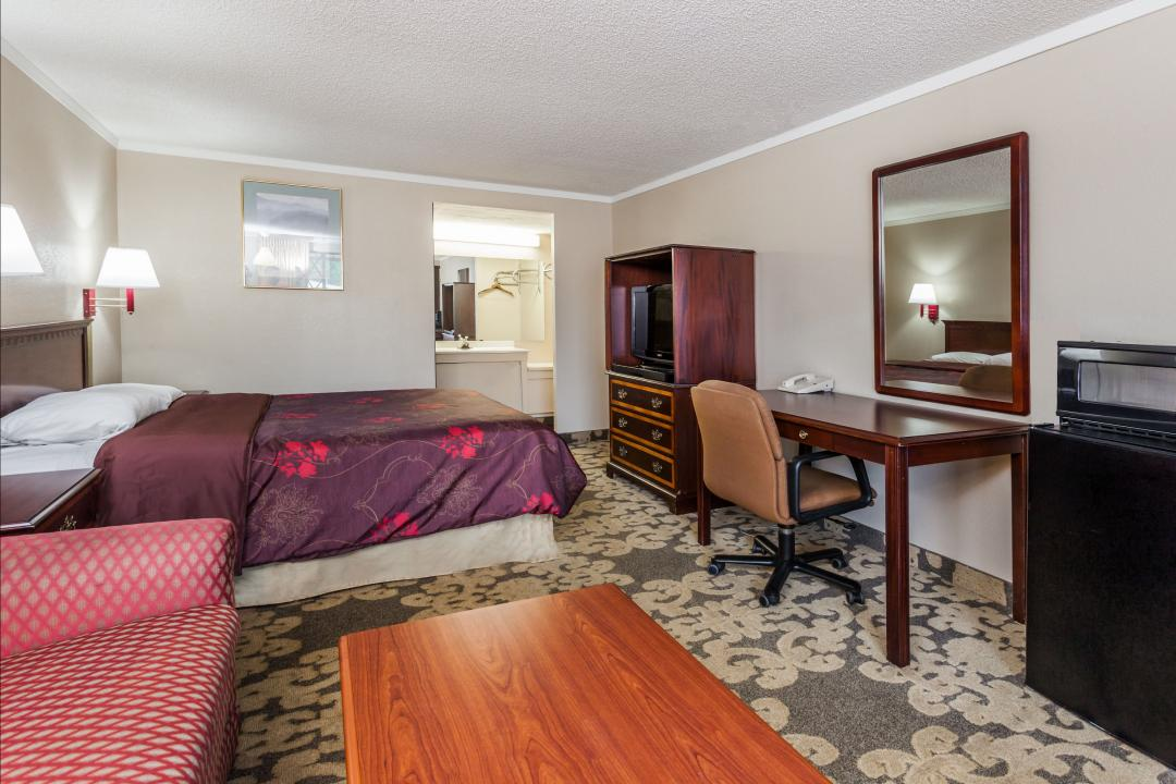 Spacious king guest room with desk and chair, refrigerator, microwave, sofa and flat screen TV