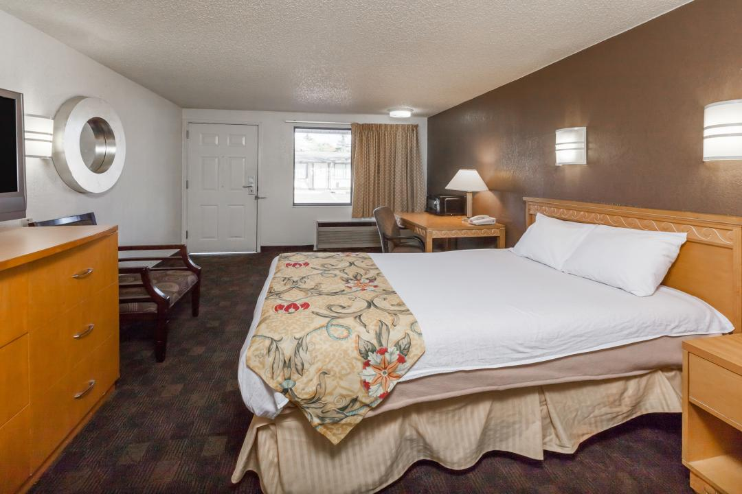 Guest room with king bed, dresser, desk, and chair