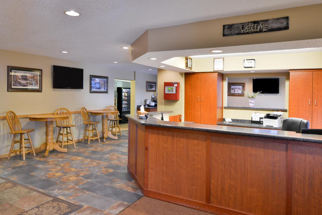 Front desk and lobby with tables and chairs