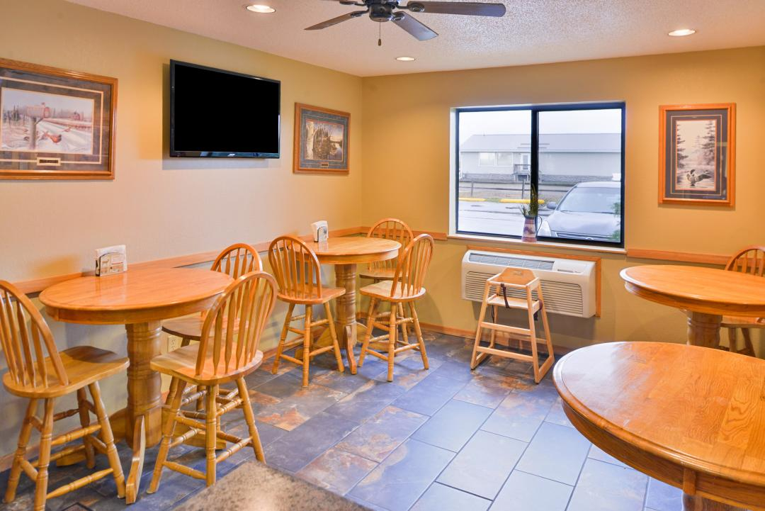 Dining Area with wooden tables and chairs, TV, and window