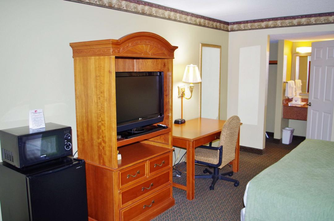 View of our One King Bed Amenities including a TV, Microwave, Micro Fridge, and Desk with Lamp.