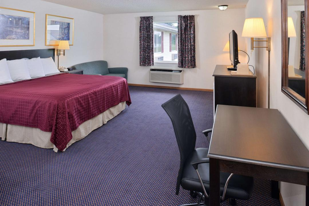 Guest Room with One King Bed and desk with task chair and flat panel TV on TV stand