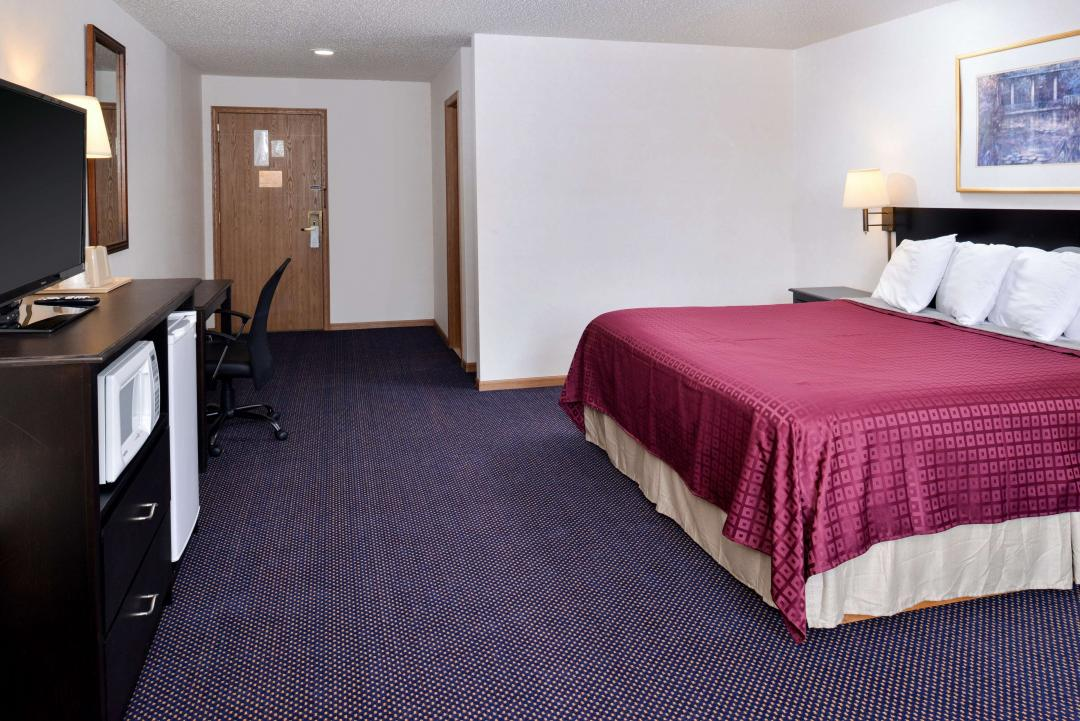 Guest Room with One King Bed , desk and chair, flat panel TV, microwave and refrigerator