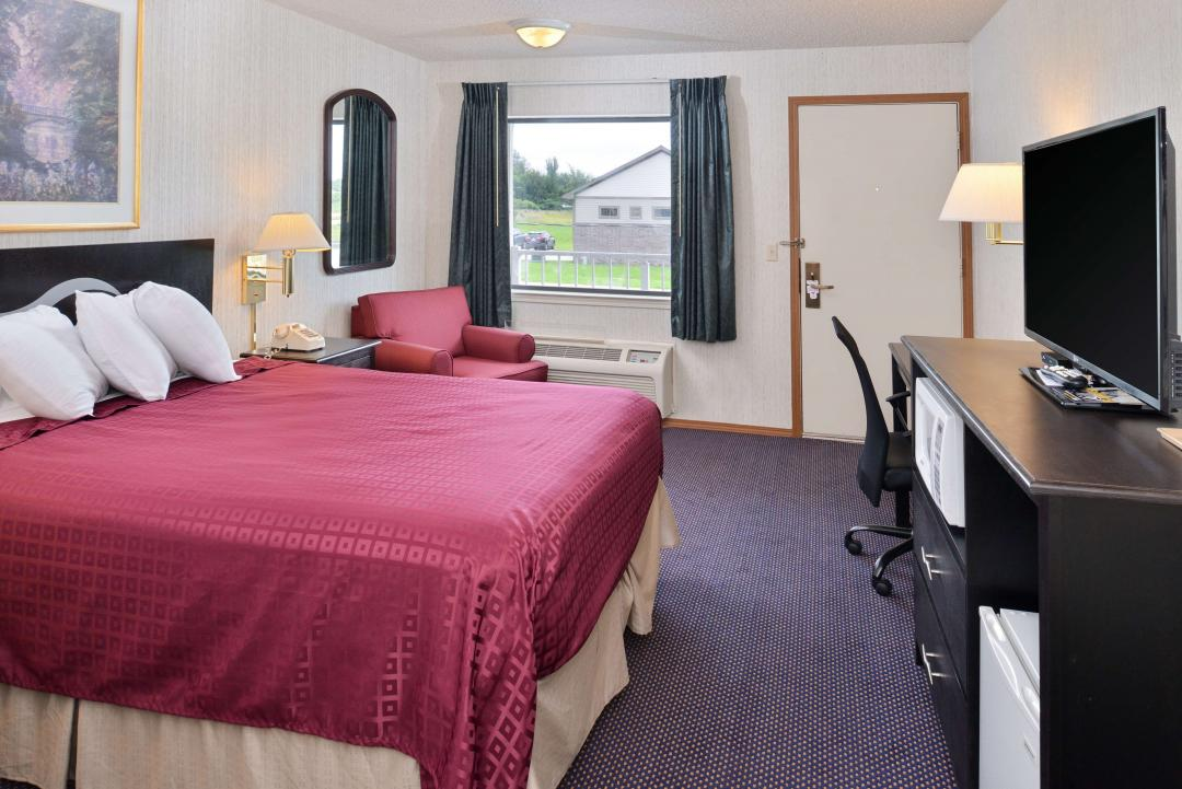 Guest Room with One Queen Bed with a lounge chair, flat panel TV, a microwave and refigerator