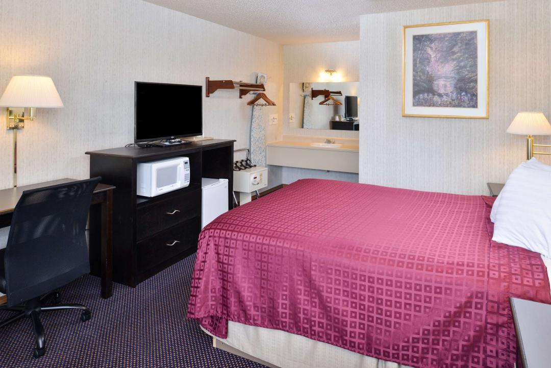 Guest Room with One Queen Bed, desk, flat panel TV, microwave and refigerator