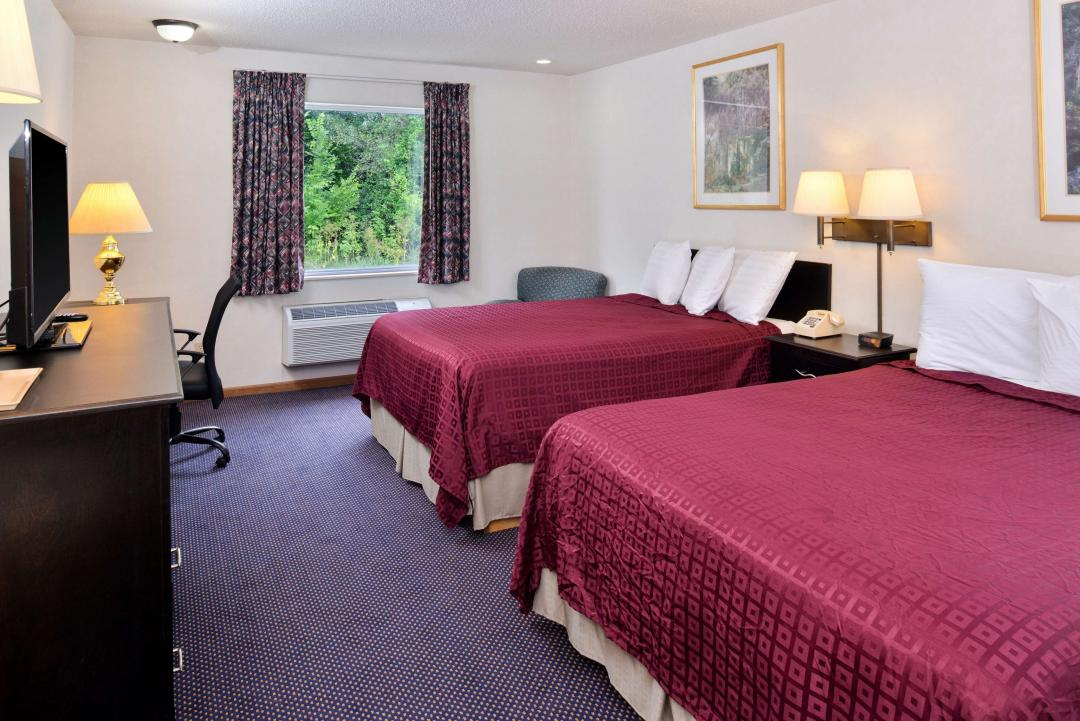 Guest Room with a wondow and Two Queen Beds, side tables and a flat panel TV on a TV stand