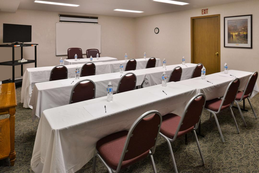 Meeting room with long tables, chairs, white board, and TV