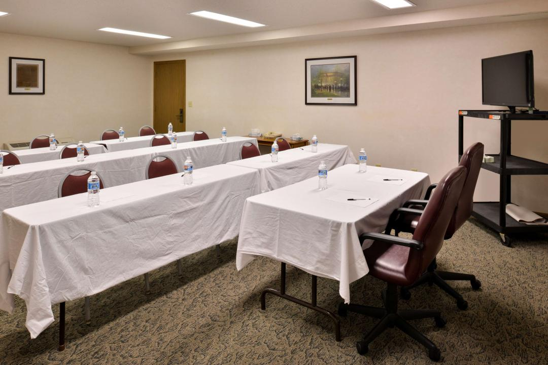 Group Meeting Room with long tables with white table cloths, chairs and flat panel TV on cart