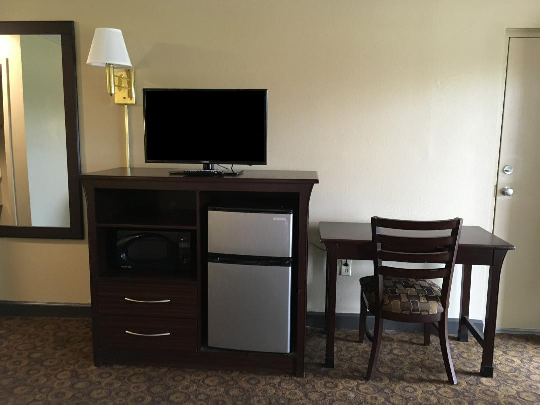 Guest Room with Mini-Fridge, Desk and Chair, Microwave, and Mirrror