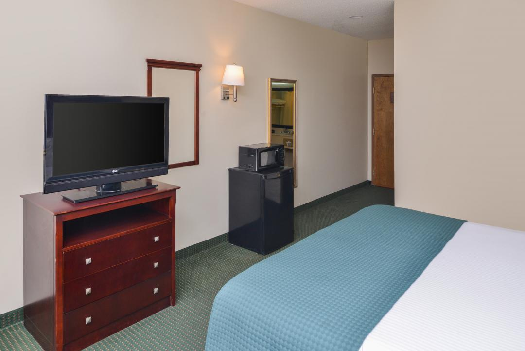 Spacious Accessible Guest Room with One King Bed with a TV, Microwave, and a Micro-Fridge.