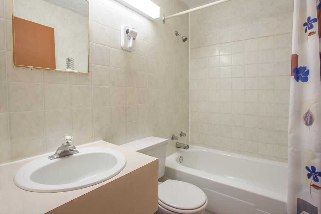 Clean, well lit guest room bathroom with sink and bathtub