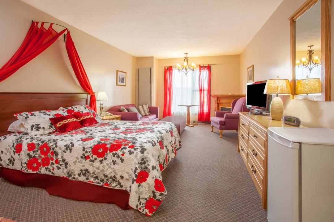 Spacious guest room with one king bed, sofa, table and fireplace