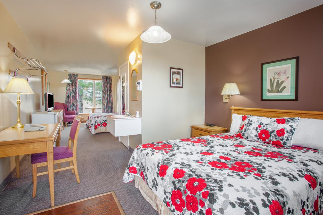 Spacious guest suite with two queen beds, armchair and desk