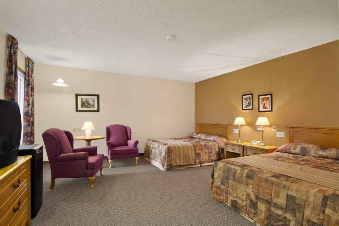 Spacious guest room with two queen beds, desk and armchairs