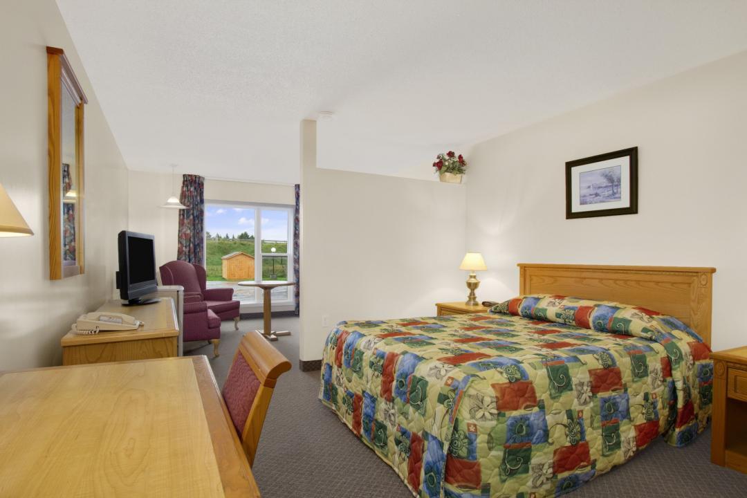 Spacious guest suite with one queen bed, armchairs and desk