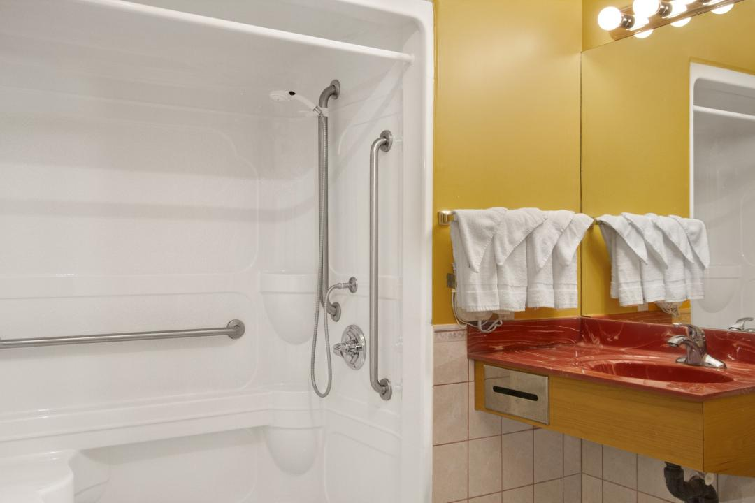 Clean, well lit guest room bathroom with sink and bathtub with grab bars