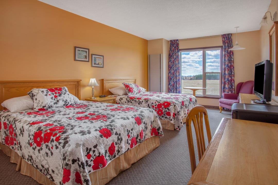 Spacious guest room with two queen beds, desk and armchair