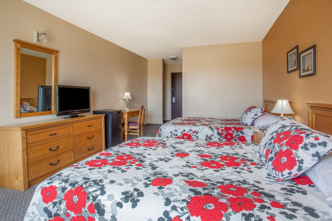 Spacious guest room with two queen beds, desk and fridge