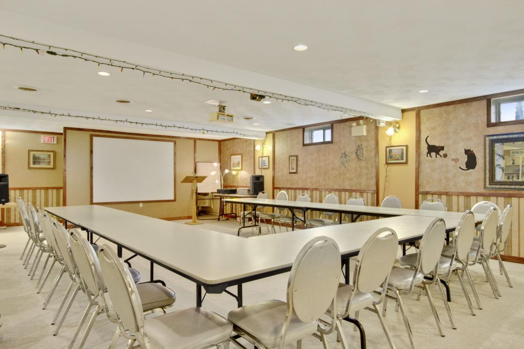 Meeting space with tables, chairs, whiteboard and speaker podium