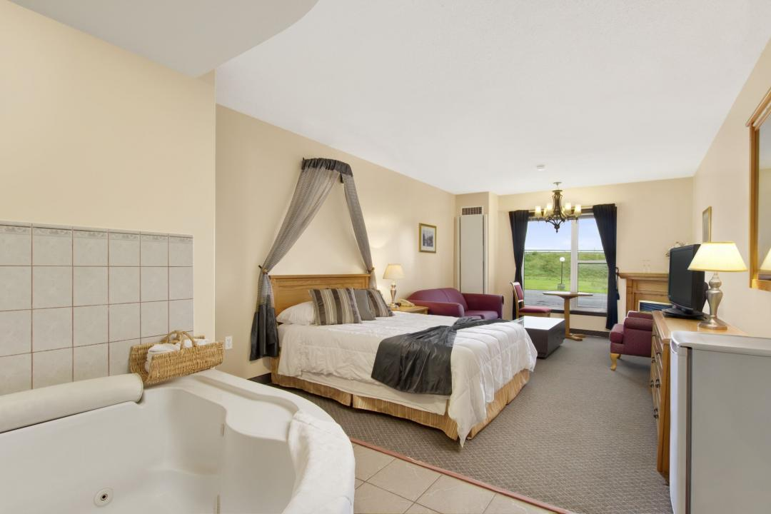 Guest room jacuzzi suite with one queen bed, sofa, table and fireplace