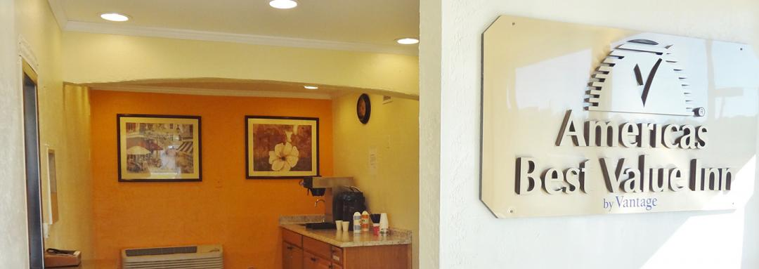Hotel lobby with sign, coffee machine, artwork, and air conditioning unit