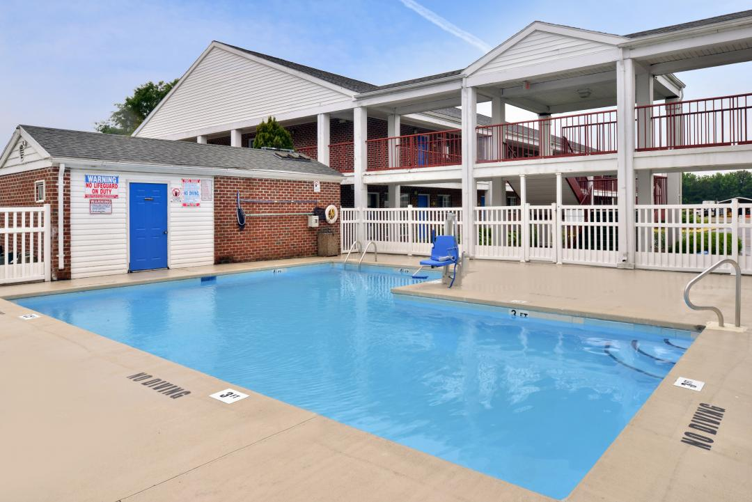 Outdoor pool area with handicap accessible lift and by exterior hotel corridor
