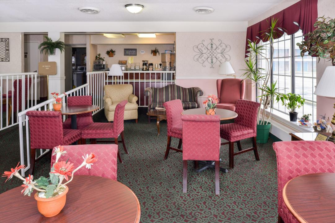 Quaint breakfast sitting area with pink chairs and tables