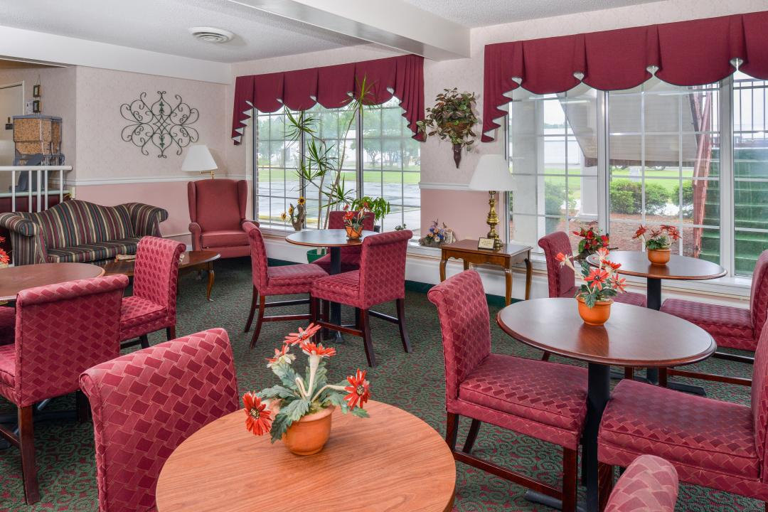 Dining room with red chairs and tables and flower center pieces