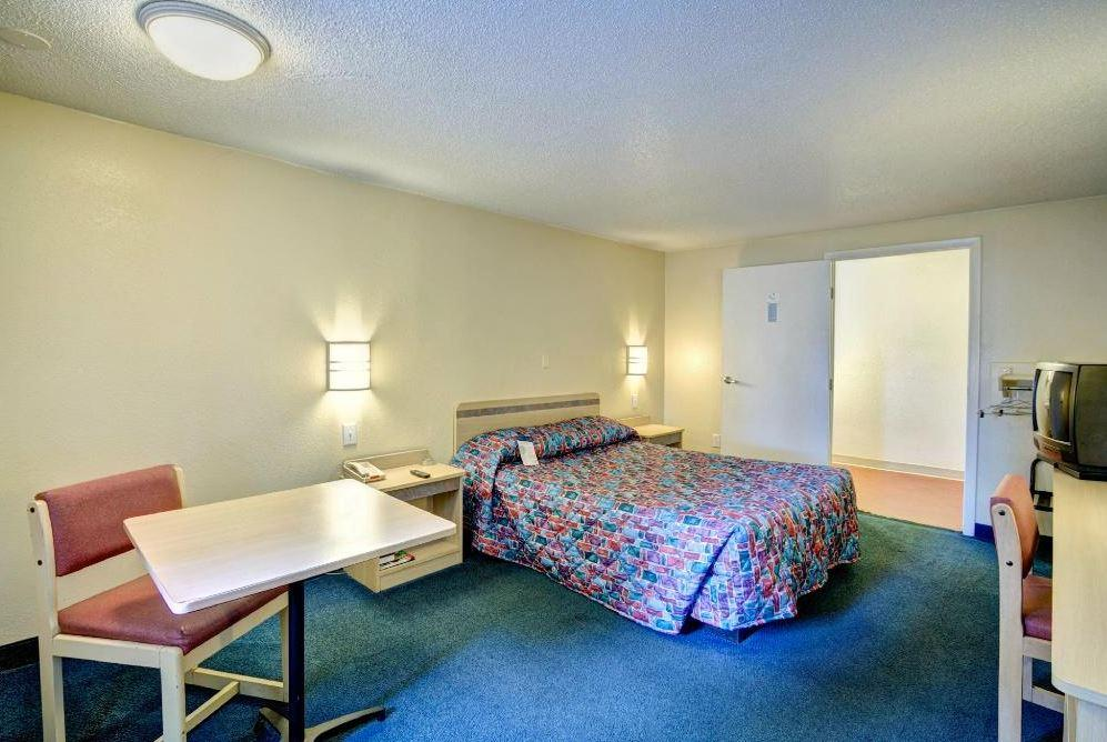Guest room with bed, table, and chair