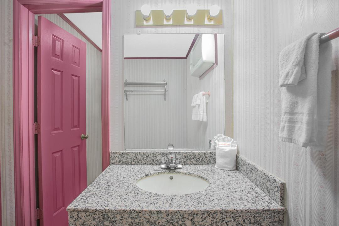 Charming, well lit guest bathroom with marble vanity and sink.