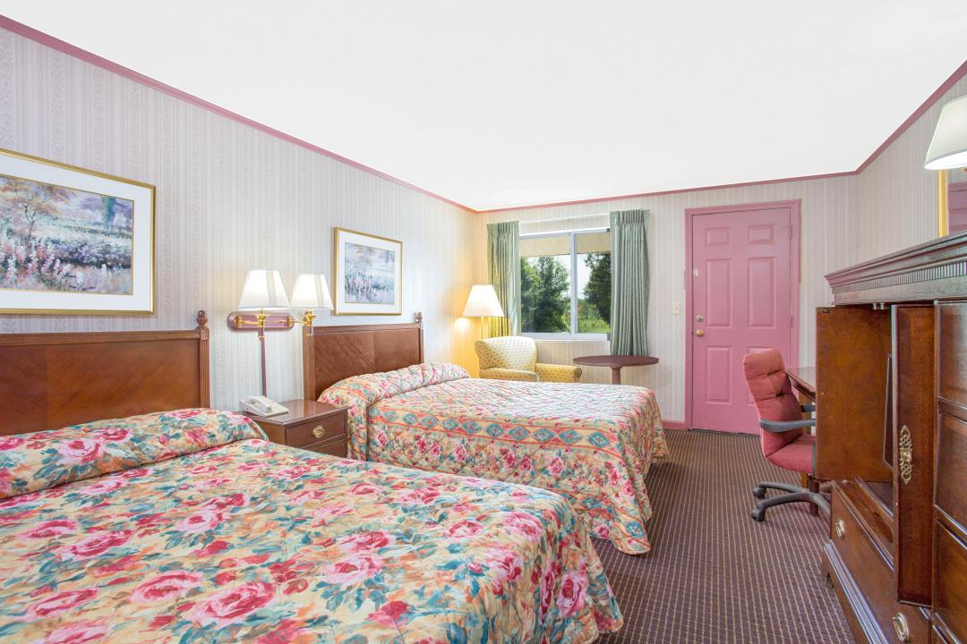 Spacious, well lit two double beds guest room with armchair, table, desk and chair.