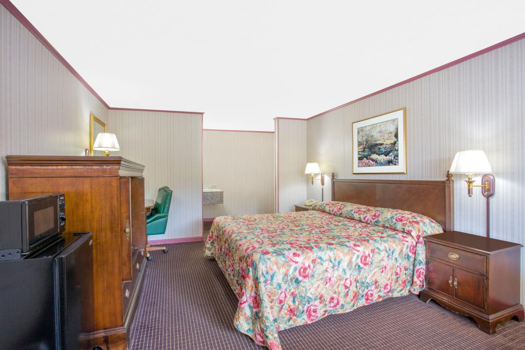 Spacious, well lit king bed guest room with desk, chair, microwave and refrigerator.