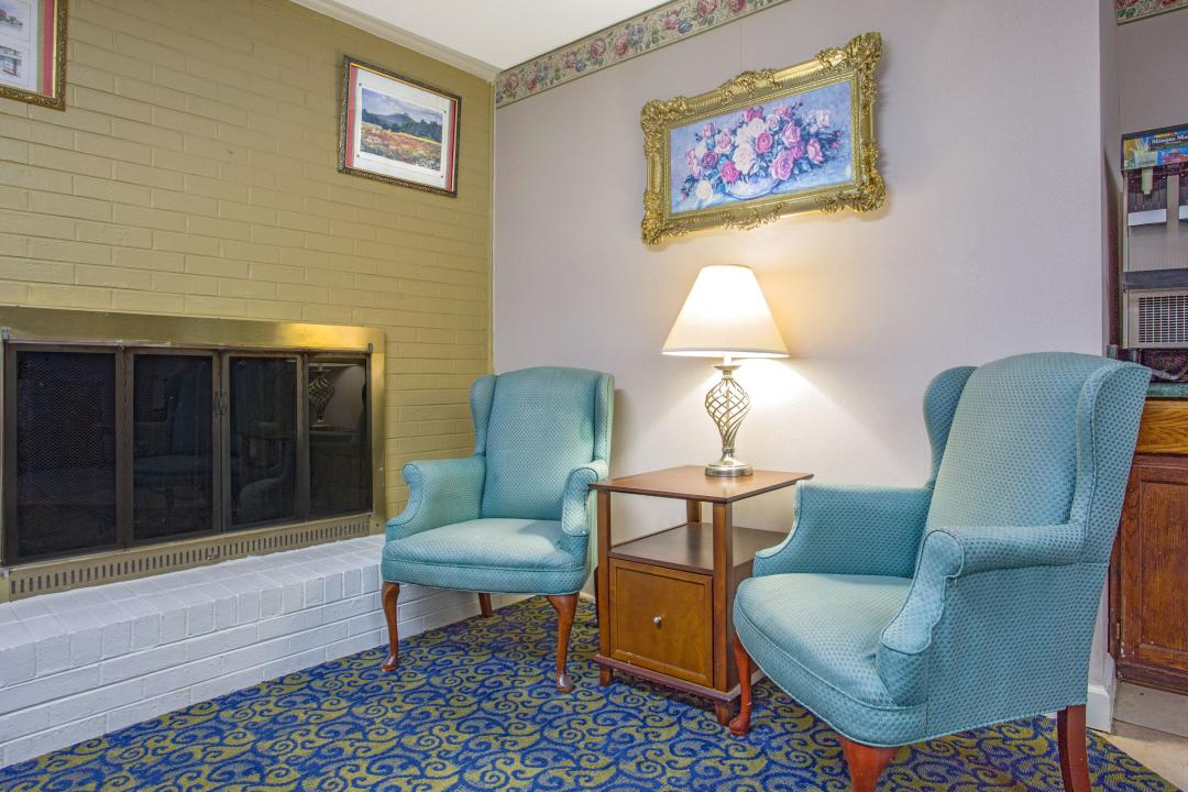 Lobby view with fireplace, armchairs, table and chairs for guest seating.