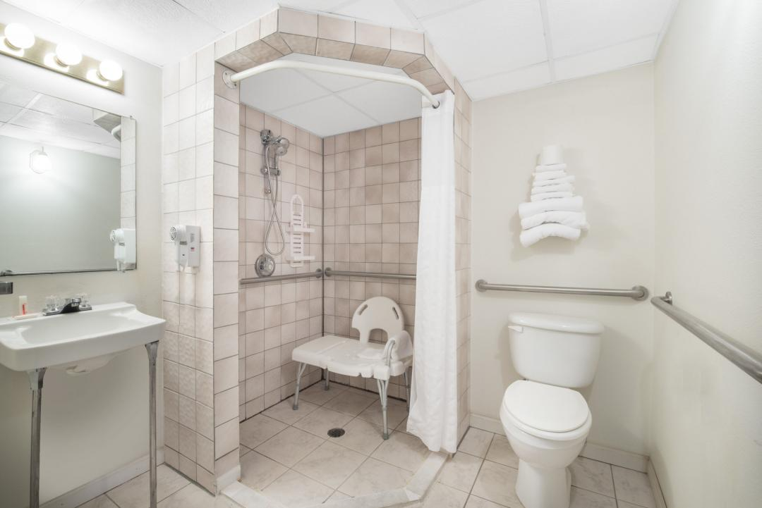 Clean, well lit accessible bathroom with sink, toilet and walk-in shower