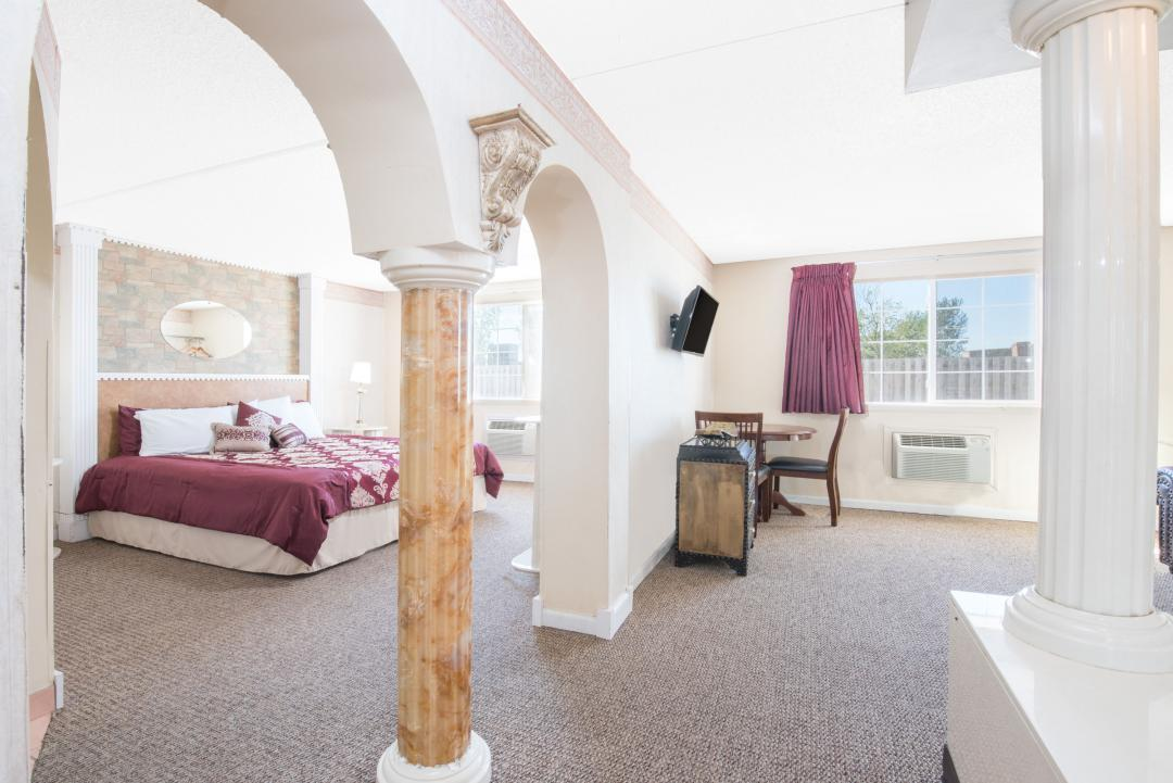 Spacious guest suite with one king bed, table and chairs