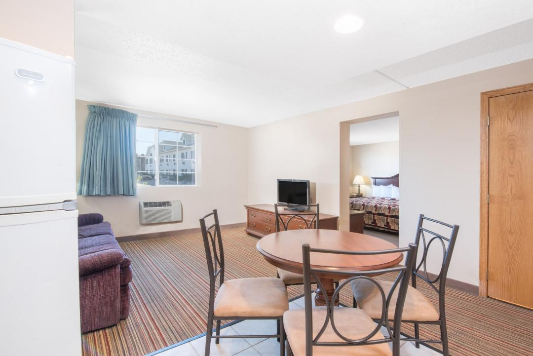 Spacious guest suite with one king bed, sofa, table and chairs