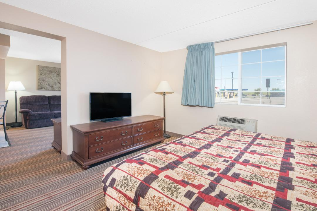 Spacious guest suite with one king bed, sofa, and chair