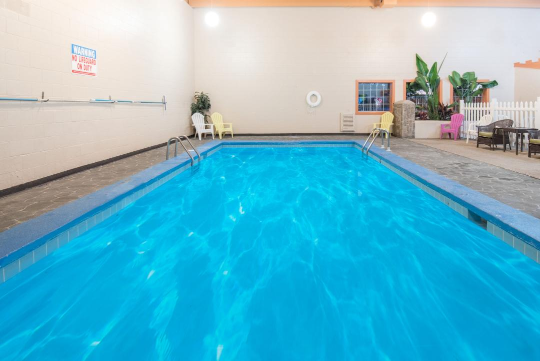 Clear blue indoor pool area with armchairs