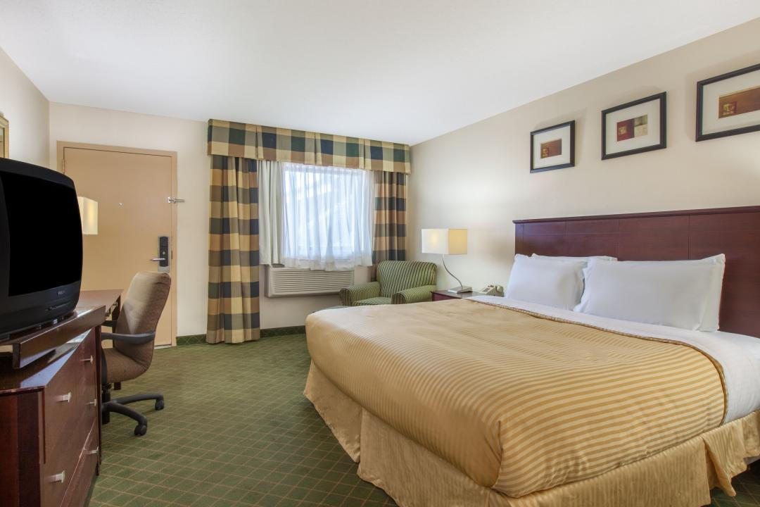 Spacious king guest room with desk, armchairs, air conditioning and television