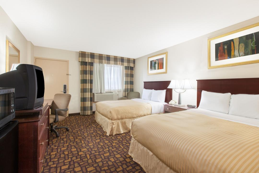 Spacious two queen guest room with desk, armchair, air conditioning and television