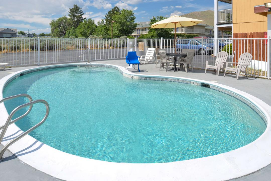 Fenced in pool with handicap lift and a table with chair and sunchairs